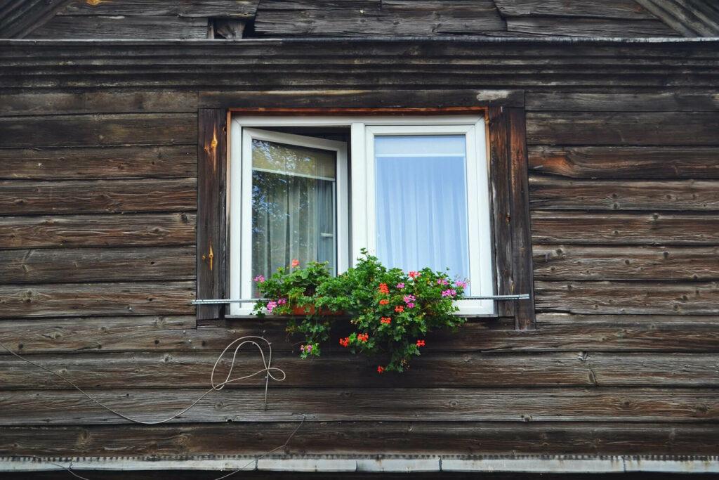 Fenster von einem Holzhaus mit Blumen auf dem Fensterbrett