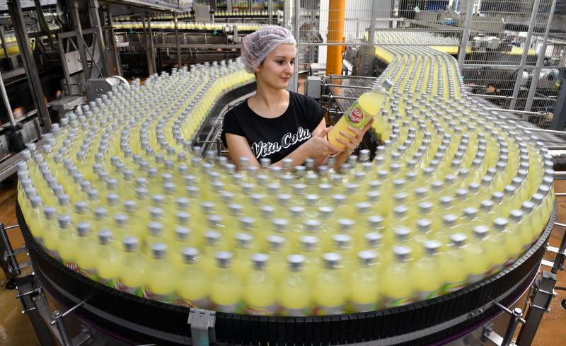Eine Frau steht mit einer Flasche Vita-Cola in der Hand bei einem Lieferband.