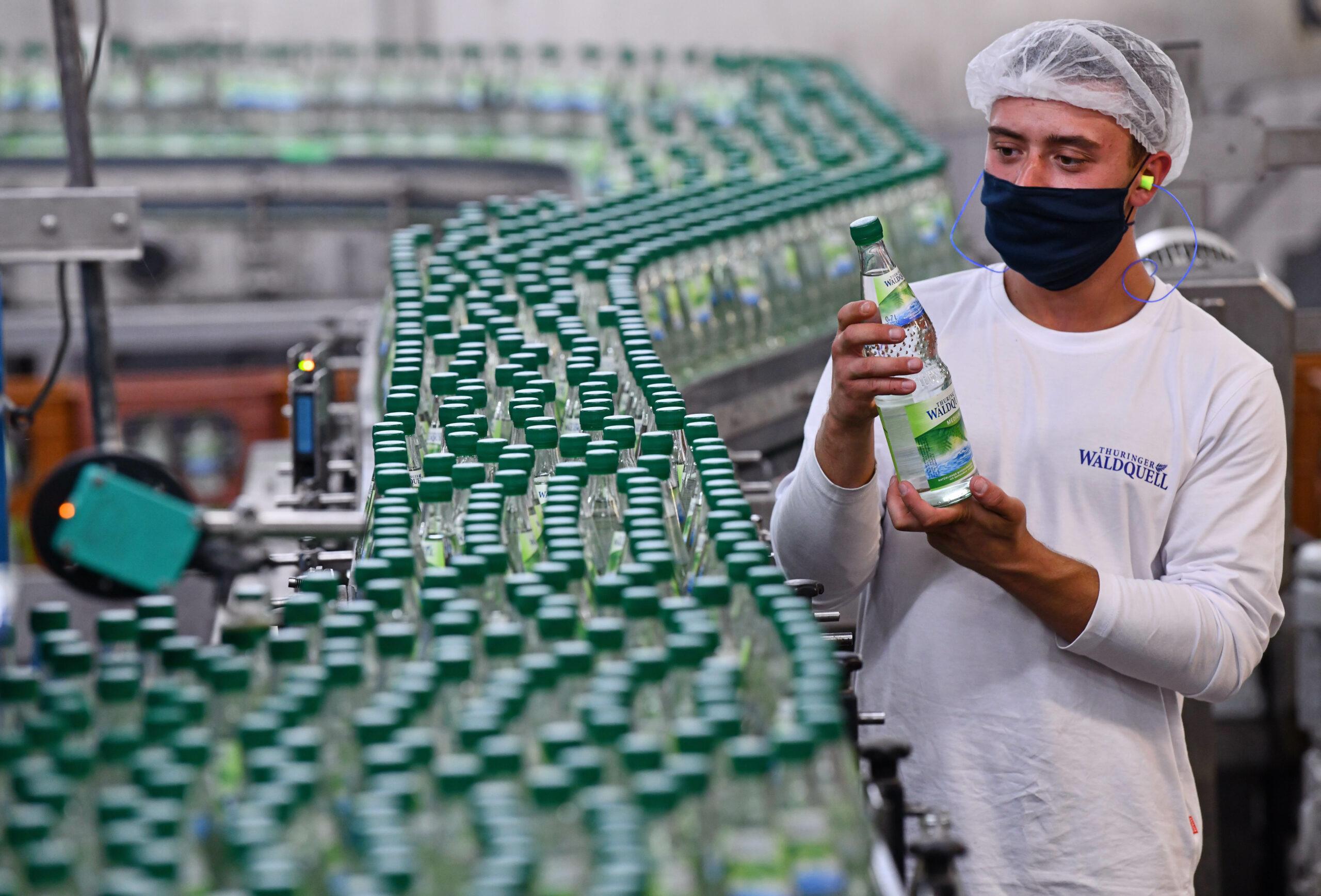Ein Mann kontrolliert eine Mineralwasserflasche von Thüringer Waldquell.