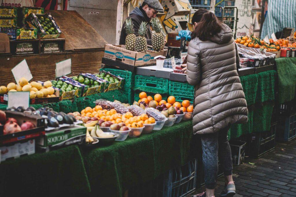 Eine Frau steht an einem Marktstand und kauft Obst.