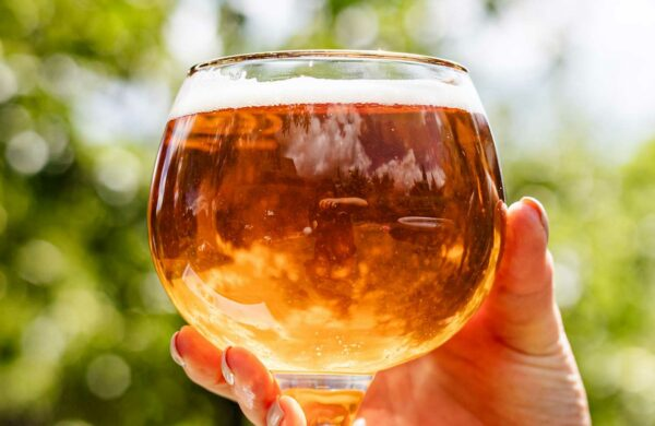 Eine Person hält ein rundes Bierglas