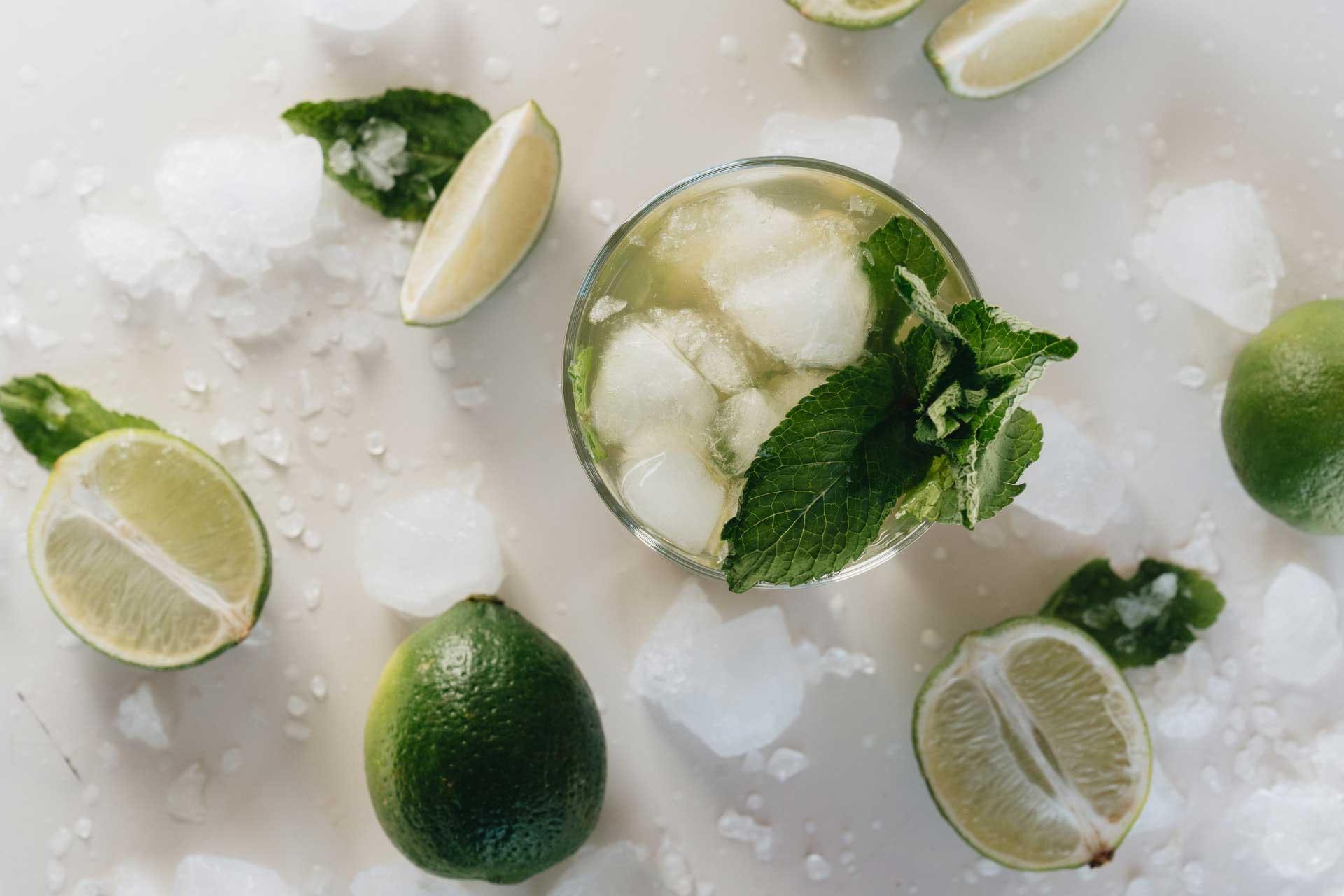 Ein Glas Maibowle mit Minze, Limettenspalten und Eiswürfeln