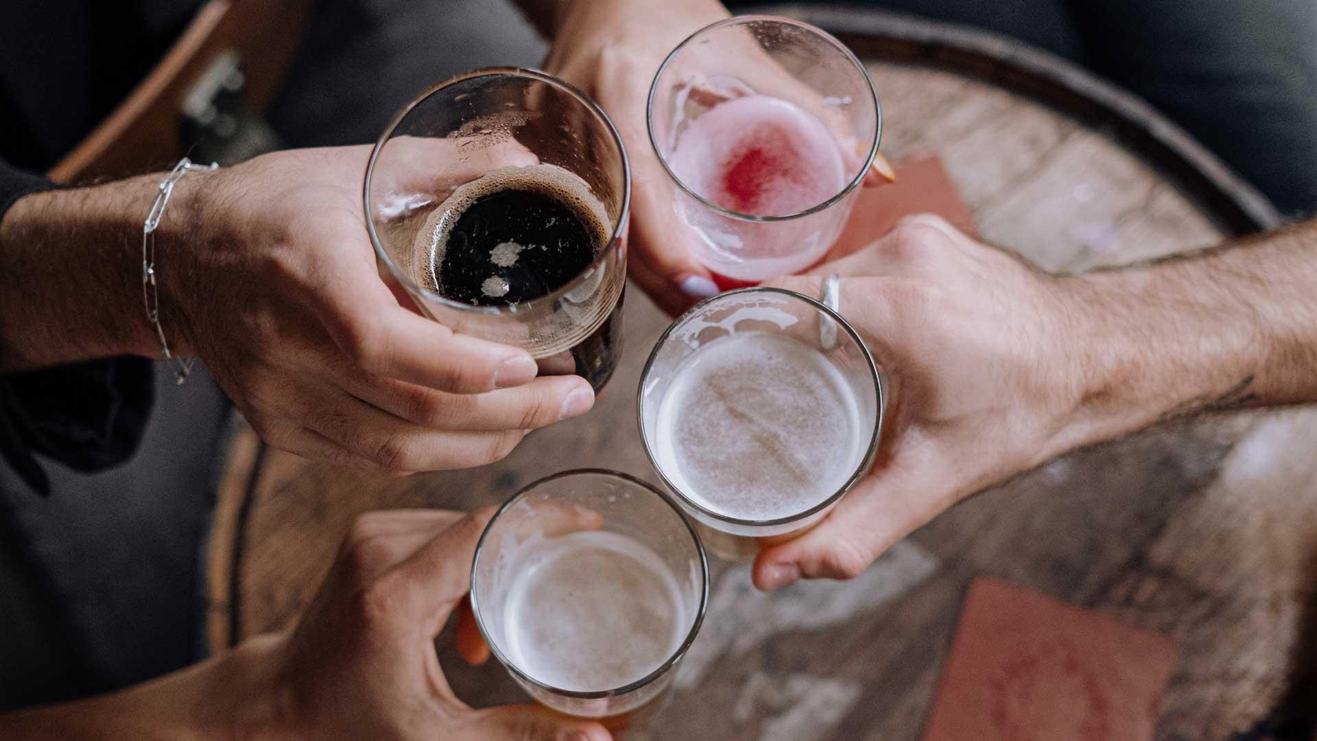 Vier Personen halten Gläser mit verschiedenen Biersorten in die Bildmitte