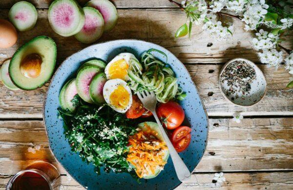 Eine Schüssel mit Ei und Gemüse, daneben ein Zweig mit Blüten und einer halben Avocado