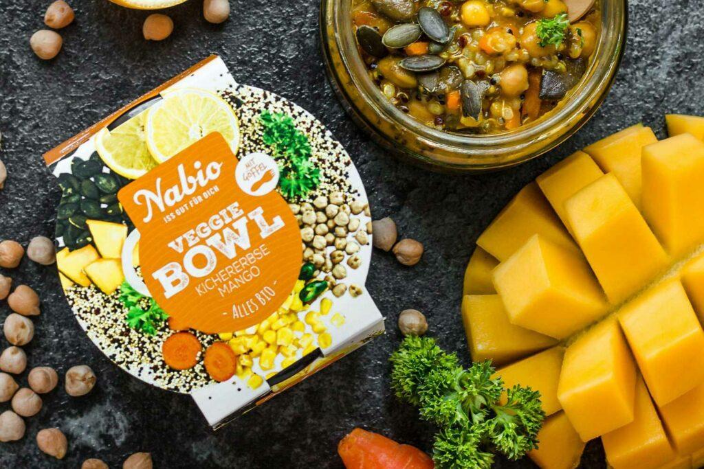 Eine Veggie Bowl von Nabio neben einer aufgeschnittenen Mango und verschiedenem Gemüse