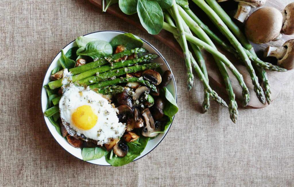 Schüssel, gefüllt mit Spinat, Kartoffeln, Pilzen, Spargel und einem Spiegelei