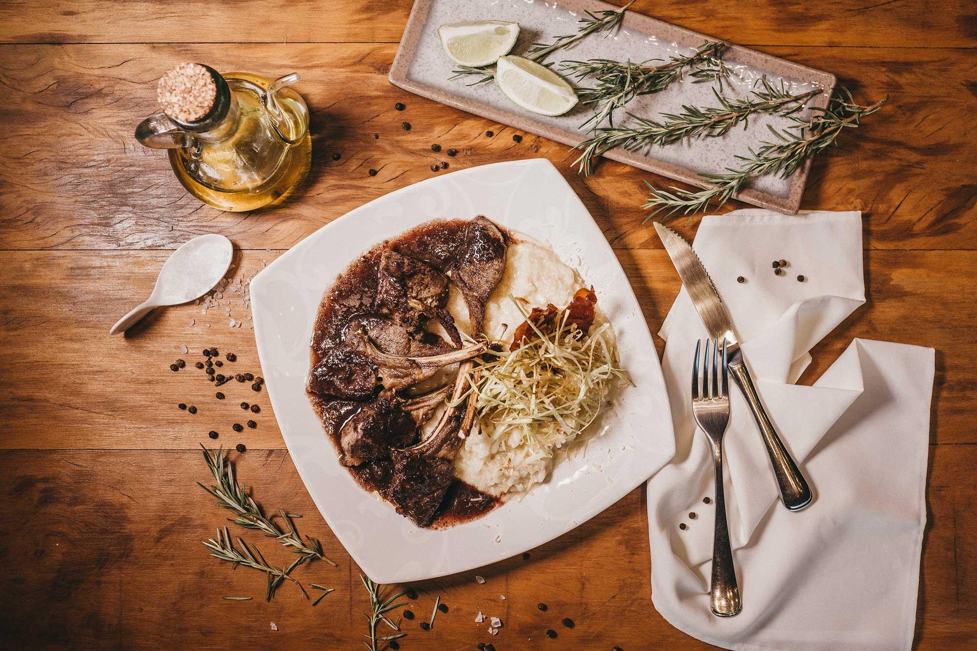 Teller mit Speisen auf einem Holztisch mit Kräutern und Öl