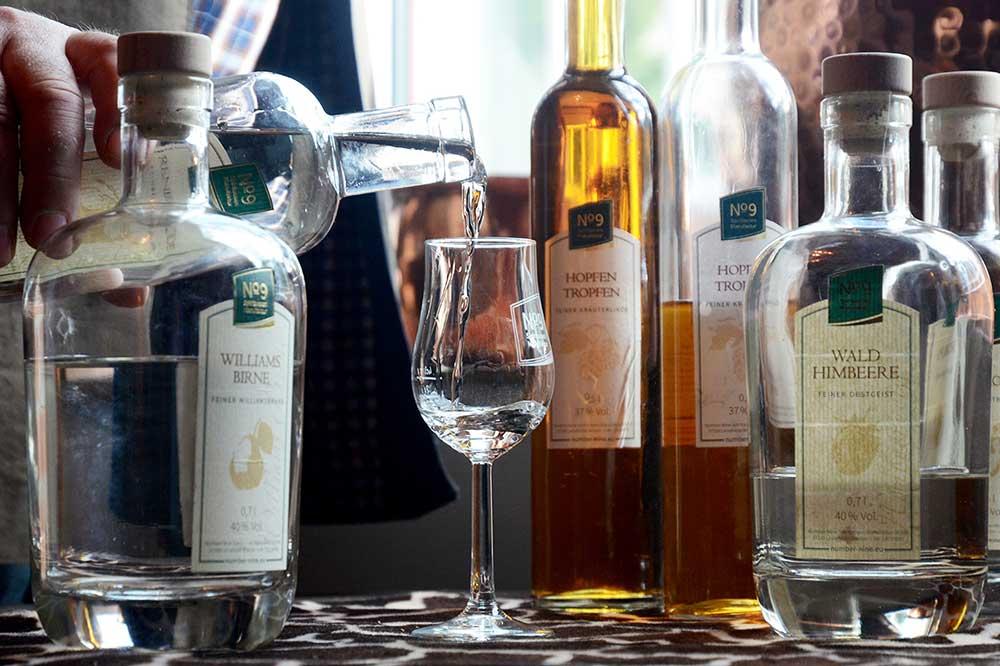 Verschiedene Glasflaschen mit alkoholischem Inhalt auf einem Tisch