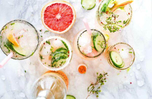 Vier Gläser mit Gin Tonic, dekoriert mit Gurkenscheiben, Grapefruit und Eiswürfeln