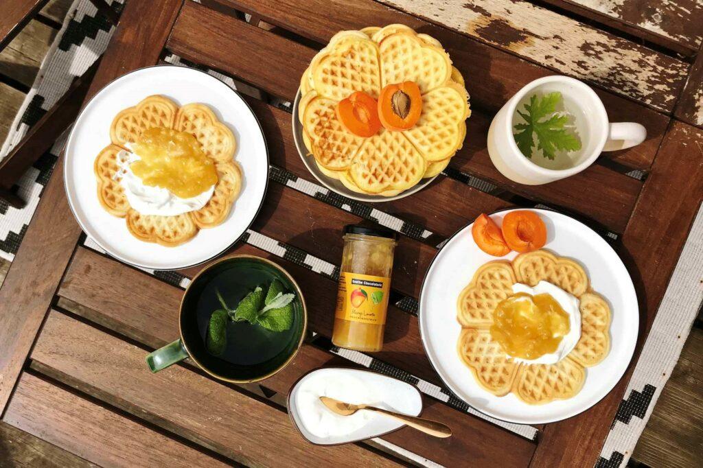Gedeckter Tisch mit Waffeln, Tee, Aprikosen, Marmelade und Joghurt